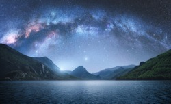 Arched Milky Way over the beautiful mountains and blue sea at night in summer. Colorful landscape with bright starry sky with Milky Way arch, moonlight, constellation, water. Galaxy. Nature and space