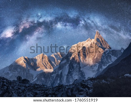 Arched Milky Way over the beautiful mountains at night in Himalayas, Nepal. Colorful space landscape with blue starry sky with Milky Way arch, snowy mountain peak. Galaxy, stars and rocks. Nature