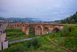 Arched old brick railway bridge in the picturesque mountains among the forest of meadows tourist trail Carpathians