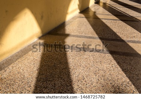 Arched passageway (arcade) in Bologna, Italy: columns are casting long shadows on terrazzo floor and yellow wall. #1468725782