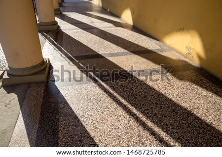 Arched passageway (arcade) in Bologna, Italy: columns are casting long shadows on terrazzo floor and yellow wall. #1468725785