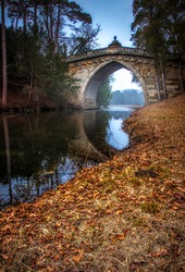 Arched stone bridge in autumn forest. Forest river bridge in autumn. Autumn forest river bridge view. River bridge in autumn forest