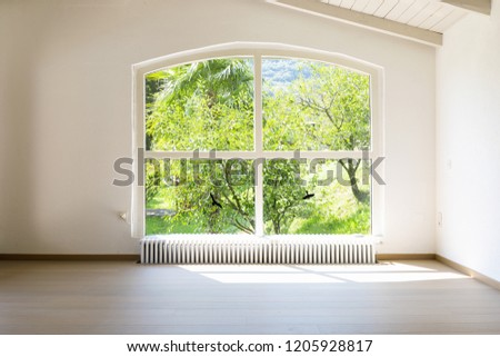 Arched window overlooking the garden. Nobody inside