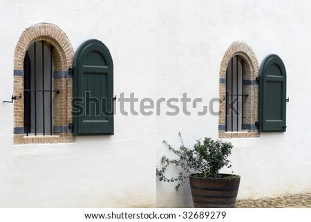 Arched windows with green wooden shutters of Cape Dutch homestead in Constantia, Cape Town, South Africa
