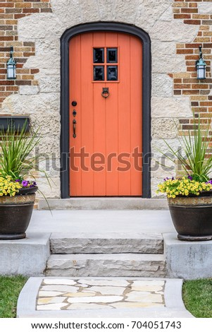 Arched wood doorway with orange front door and inviting front entrance and curb appeal #704051743