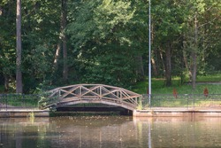 Arched wooden bridge with railing across lake in city park.