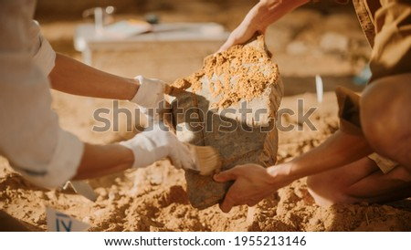 Archeological Digging Site: Two Great Archeologists Work on Excavation Site, Carefully Cleaning, Holding Newly Discovered Ancient Civilization Cultural Artifact, Historic Clay Tablet, Fossil Remains Zdjęcia stock ©
