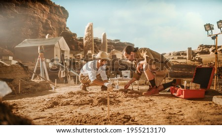 Archeological Digging Site: Two Great Archeologists Work on Excavation Site, Cleaning Cultural Artifacts with Brush and Tools. Discovery of Ancient Civilization Temple, Architecture, Fossil Remains Zdjęcia stock ©