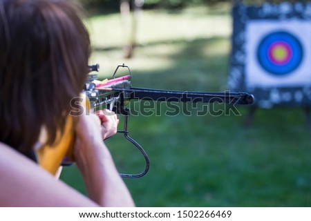 Archer crossbow arbalest with arrows ready for hitting target in bullseye on archery competition. Success concept. Aiming. Green background. #1502266469