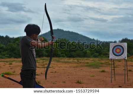 Archer hold his bow to aim at the target #1553729594