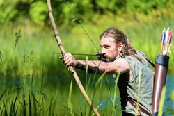Archer man shooting the bow and arrow in the swamp.Copy space