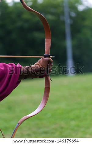 Archer prepares to shoot arrow at target.