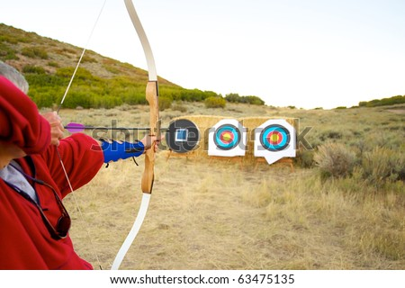 Archer prepares to shoot arrow at target.