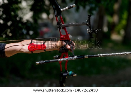 Archer pulls on the sport bow string, taking aim at his target at the competition #1407262430