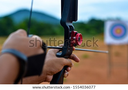 Archer's hand view aiming on the target #1554036077