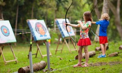 Archery for child. Little girl with bow and arrow. Kids shoot on tropical island. Target on outdoor shooting range. Archer club for young children. Healthy summer activity.