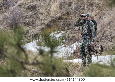 Archery hunter scouting for his next target Stockfoto ©