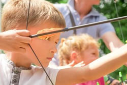 Archery junior championship. Summer sports. Summer holidays. Boy with green eyes pull the arrow. Kid stared at target. Child directed arrow at a target. Children and sports. Archery background