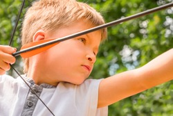 Archery school. Boy with a bow and arrow. Children and sports. Archery background. Junior archery championship. Archery for kids