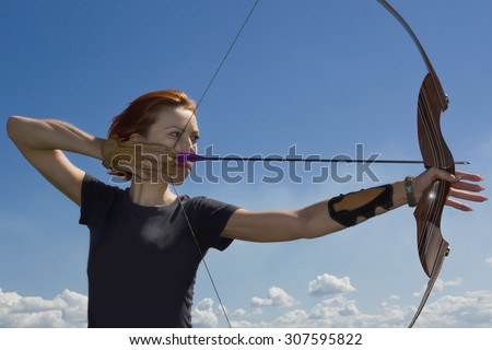 Archery woman bends bow archer target narrow in the summer field