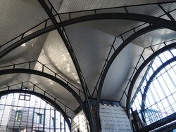 Arches and arches of the station. Metal structures under the roof of a large building. Construction supports and beams. Gothic arches indoors