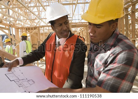 Architect and builder at construction site