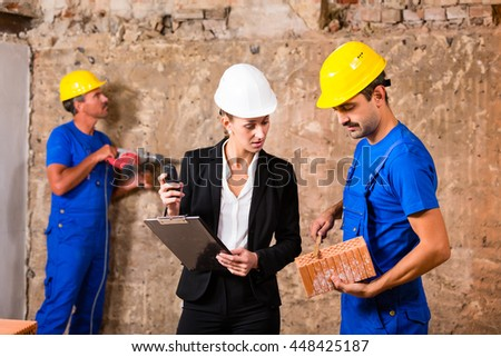 Architect and builder on construction site discussing brick and material