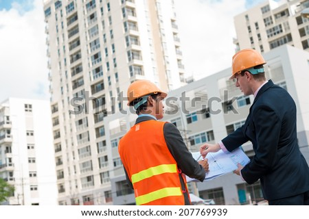 Architect and client discussing the plan of the building at the construction site, rear view