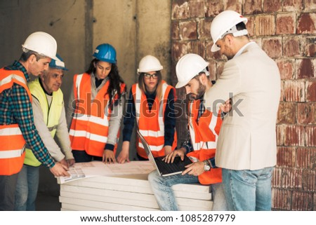 Architect and consruction workers on a construction site #1085287979