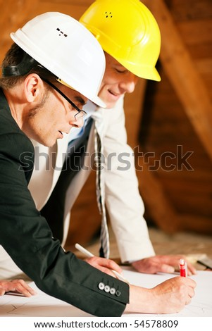 Architect and construction engineer or surveyor discussion plans and blueprints. Both are wearing hardhats and are standing on the construction site of a home indoors