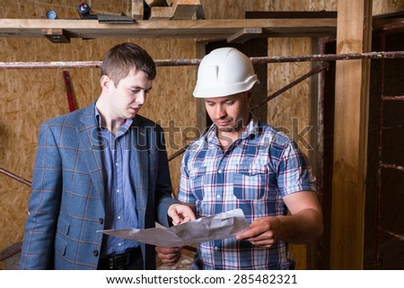 Architect and Construction Worker Foreman Inspecting Plans Together Inside Unfinished Building