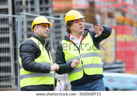 Architect and construction worker with yellow safety jacket and hardhat talking at construction site