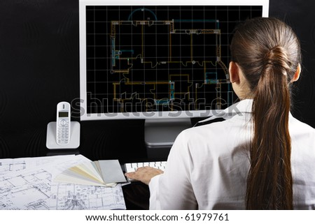 Architect at work. Architectural project on computer monitor. Blueprints on the desk.