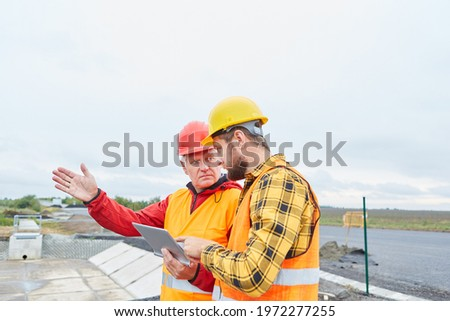 Architect discusses road construction planning with foreman using tablet computer ストックフォト ©