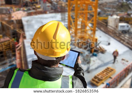 architect engineer construction worker with hard hat working on site with tablet computer