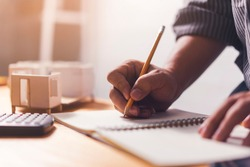 Architect engineer contractor close up working desk house model, home building house model planning idea designing hand sketching ideas on notebook and support construction structure calculation