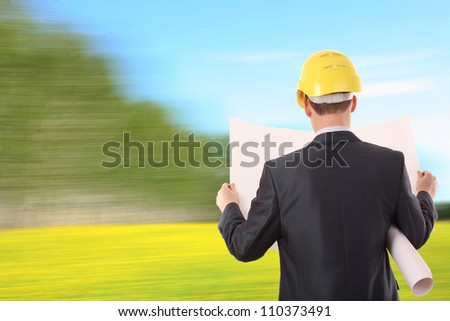 architect engineer expertise team plan talking hardhat in rapeseed field on sky background and forest trees Photo