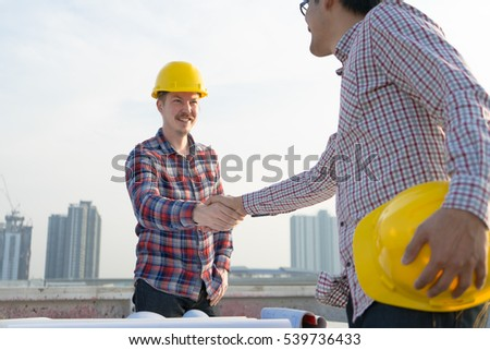 Architect engineer shaking hands other hand he is holding a helmet at construction site against clear sky. With blueprint on table. - business teamwork, cooperation, success collaboration concept