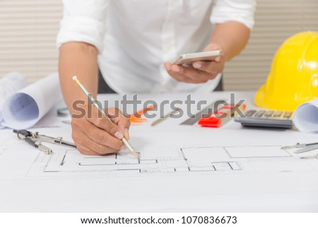 Architect hands working on blueprint plans with a pencil, a smartphone, ruler, calculator, laptop and engineering tools #1070836673