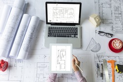 Architect hands working with tablet and laptop computer. Architectural project, roll blueprints, ruler, dividers, a small house model,glasses, a cup of coffee and engineering tools on working desk.