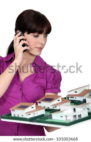 Architect holding a small-scale model while talking on the phone