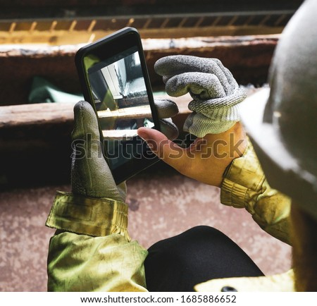 Architect holding a smartphone on construction site. young construction worker is using mobile phone on site. Construction worker with building plans and cellphone. Focus on mobile. warm vivid filter.