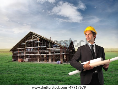 Architect holding some project with a house in construction on a green meadow on the background