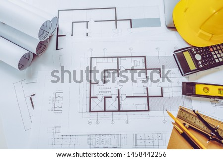 Architect house plan roled -up plans on the table, high angle view and engineer object.