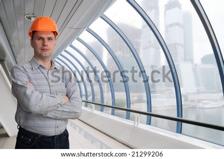 Architect in hard-hat against modern building