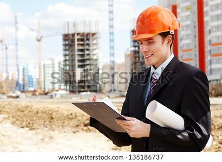 Architect in helmet writing something near  new building