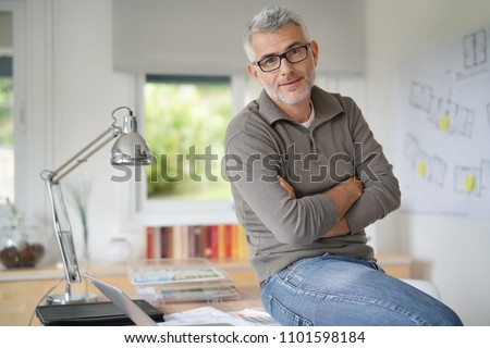Architect in office sitting on desk looking at camera