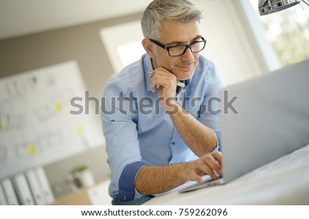 Architect in office working on construction project using laptop
