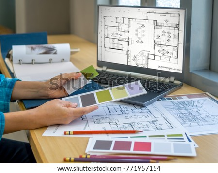 Architect (interior designer) working with drawing,  material sample & laptop computer in office / Business of Real estate, home decoration & renovation concept