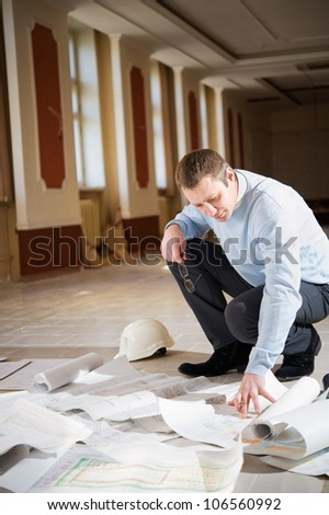 Architect looking blueprint on the floor of the reconstruction interior.